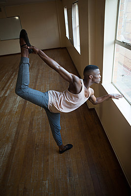Ballerino stretching on a window while practicing ballet dance - p1315m1514563 by Wavebreak