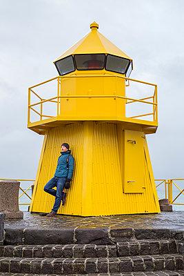 Mann lehnt an gelben Leuchtturm - p1396m1462020 von Hartmann + Beese