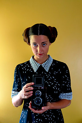 Young woman in retro dress and old camera - p1521m2108373 by Charlotte Zobel