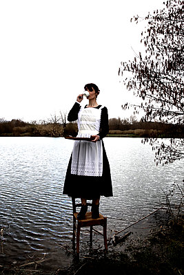 Maid drinks tea and standing on a chair - p1521m2158322 by Charlotte Zobel