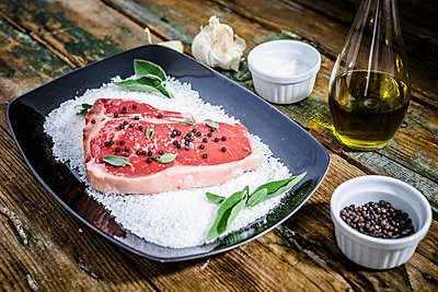Raw beefsteak with rosemary, salt and pepper - p300m1535679 by Giorgio Fochesato