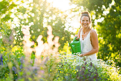 Portrait of young woman watering flowers in springtime garden - p300m2264654 by Annika List