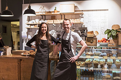 Portrait of smiling male and female partners standing at store - p426m2036282 by Kentaroo Tryman
