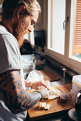Bearded tattooed man with long brunette hair standing in a kitchen, preparing food. - p429m2202181 by Eugenio Marongiu