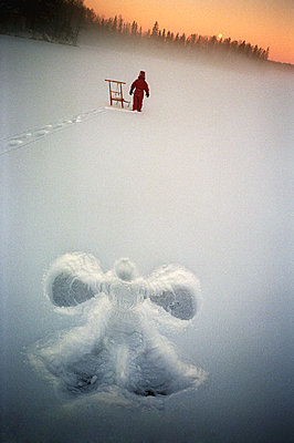 Snow Angel And Boy On Snowy Winter Landscape, Sweden  - p847m1529542 by Mikael Andersson