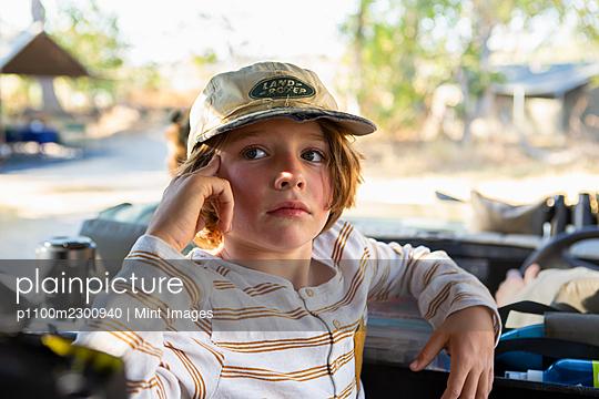 Young boy in safari vehicle at sunrise, Okavango Delta, Botswana. - p1100m2300940 by Mint Images