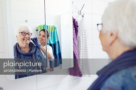 Nurse combing woman's hair in bathroom - p312m2299652 by Plattform