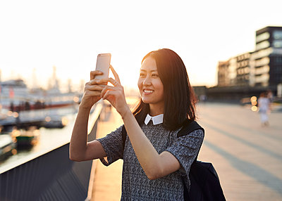 Asiatin macht ein Foto mit Smartphone - p1124m1169901 von Willing-Holtz