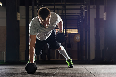 Determined male athlete doing push-ups while lifting dumbbells in gym - p1166m1154103 by Cavan Images