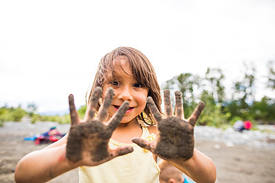 Girl showing dirty hands with mud - p1166m2201994 by Christopher Kimmel / Alpine Edge Photography