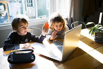 kids in morning light sitting at table doing remote school - p1166m2232757 by Cavan Images