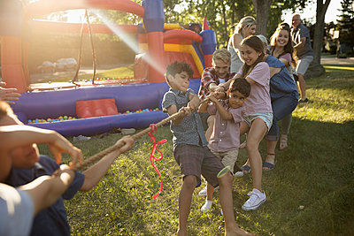 Kids playing tug-of-war at summer neighborhood block party in sunny park - p1192m2017058 by Hero Images