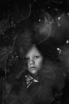 Monochrome portrait of a child in the foliage - p1642m2216209 by V-fokuse