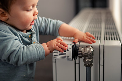 Baby boy playing with thermostat of heater - p300m2084074 by Sebastian Dorn
