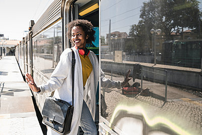 Smiling young woman entering a train - p300m2155852 by Uwe Umstätter