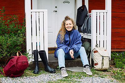 Portrait of smiling mid adult woman with backpacks and boots sitting outside cottage - p426m2117197 by Maskot