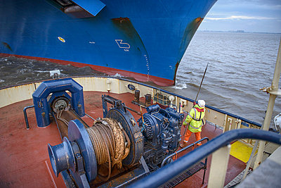 Tugboat worker catching rope on deck - p429m747077f by Monty Rakusen