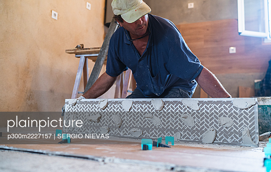 Mature man putting hardwood on floor in house - p300m2227157 by SERGIO NIEVAS