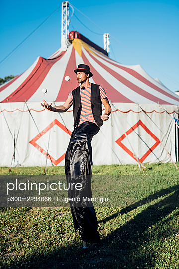 Male circus performer juggling balls while standing with stilts on meadow - p300m2294066 by Eugenio Marongiu