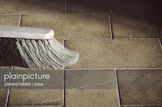 Old broom on tile floor - p564m2108403 by Dona