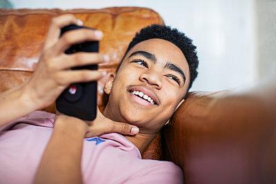 Smiling teenage boy using smart phone on sofa - p1023m2136170 by Sam Edwards