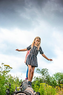 Two Young Girls Walking on a Log - p1166m2207809 by Cavan Images