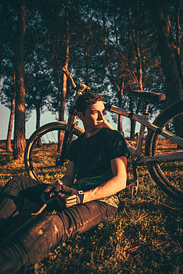 Thoughtful young man sitting by bicycle in park during sunset - p300m2206495 by Aitor Carrera Porté