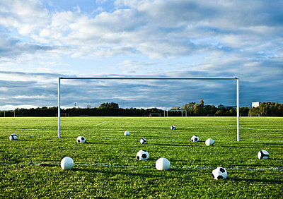 Footballs on empty pitch - p92411449 by Dean Northcott