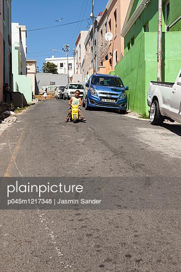 Afrikanischer Junge fährt auf Roller - p045m1217348 von Jasmin Sander