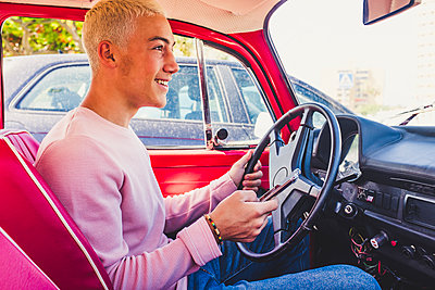 Smiling teenage boy sitting in vintage car with smartphone - p300m2203098 by Simona Pilolla