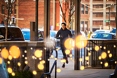 Woman jogging in city - p343m2046946 by Josh Campbell