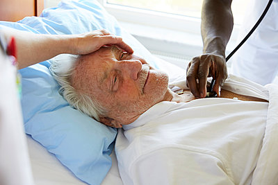 Cropped image of female nurse consoling senior man while male colleague examining with stethoscope in hospital ward - p426m1494049 by Maskot