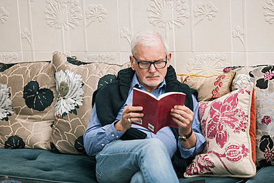 Senior man reading book on couch - p429m1206854 by Colin Hawkins
