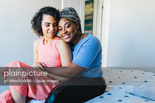 Portrait of cheerful woman embracing girlfriend while sitting on bed - p1166m2130590 by Cavan Images