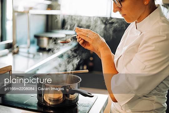 Female chef seasoning hot food while standing at stove - p1166m2208084 by Cavan Images