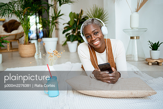 Smiling woman with mobile phone listening music through headphones while lying on rug in living room - p300m2276381 by Rafa Cortés