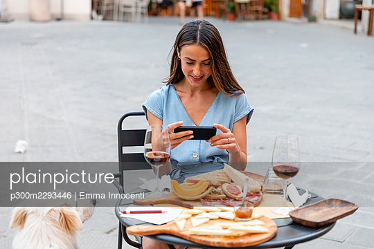 Smiling woman photographing food and drink at sidewalk cafe - p300m2293446 by Emma Innocenti