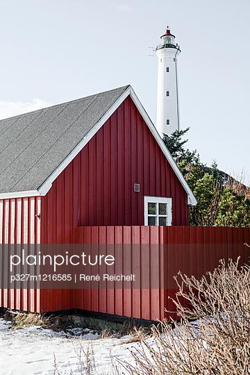 Rotes Holzhaus vor weißem Leuchtturm - p327m1216585 von René Reichelt