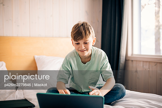 Blond boy E-learning through laptop at home - p426m2279846 by Maskot