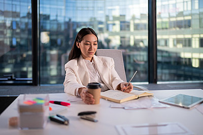 Asian businesswoman making notes in office - p1166m2279417 by Cavan Images