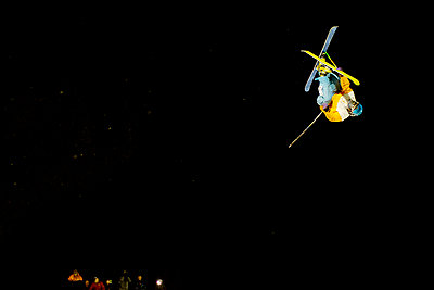 Man performing freestyle skiing jump at night - p1166m979980f by Cavan Images