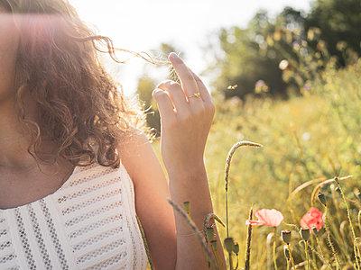 Teenage girl in summer in a flowering meadow - p1564m2294933 by wpsteinheisser