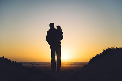 USA, California, Morro Bay, silhouettes of father and baby enjoying sunset on the beach - p300m1587796 von Gemma Ferrando