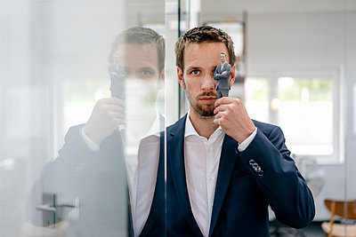 Businessman holding his 3D portrait in front of his eye - p300m2058792 by Flamingo photography