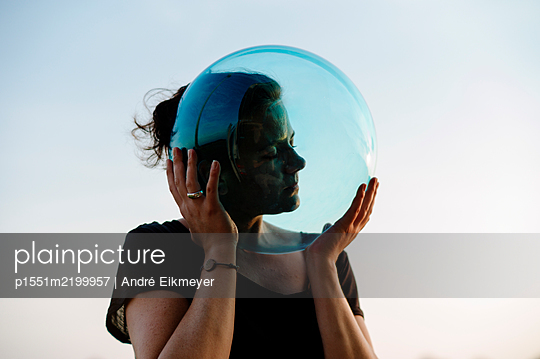 Woman holding glass ball - p1551m2199957 by André Eikmeyer