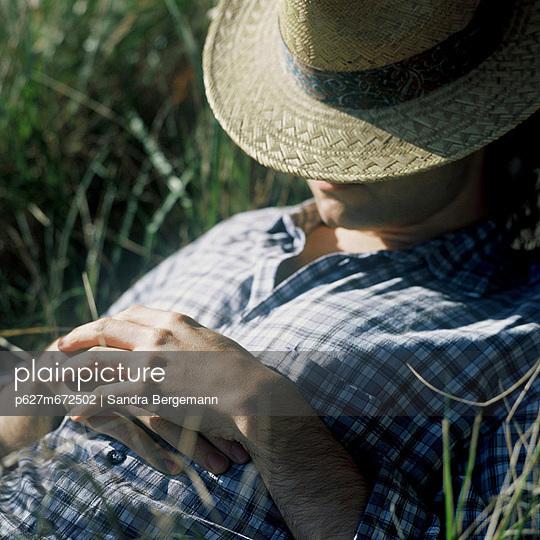 junger mann mit strohhut schlafend - p627m672502 by Sandra Bergemann