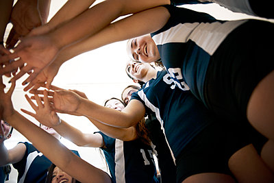 Low angle view of teenage girls huddling in court - p1166m1087813f by Andrew Lipovsky