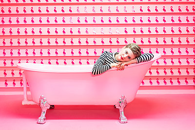 Woman lying in a bathtub in front of pink coloured background - p1332m2055061 by Tamboly