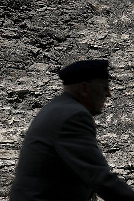 Alter Mann passiert Steinmauer - p1650m2230889 von Hanna Sachau