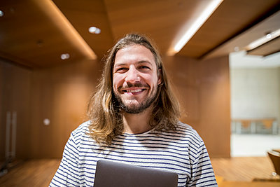 Portrait of laughing man with laptop in university - p300m1549912 by Jo Kirchherr